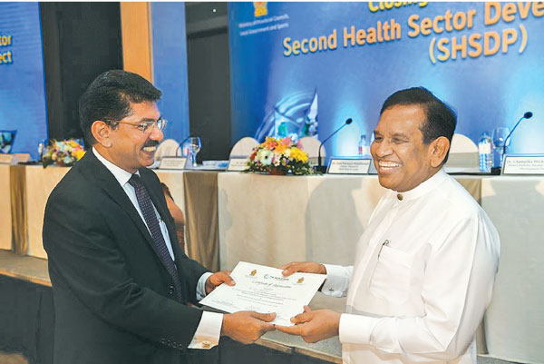 Health Minister Dr.Rajitha Senaratne presenting a certificate to Health Services Director General Dr.Anil Jasinghe.