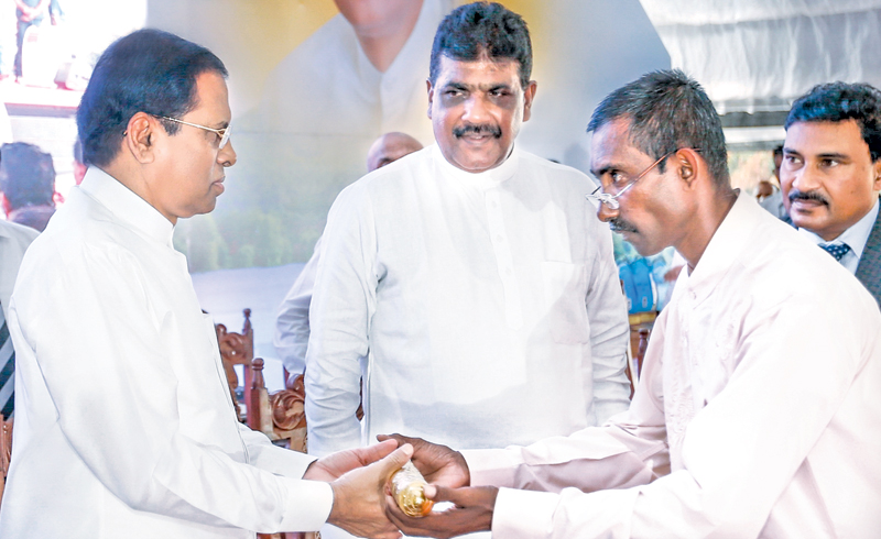 President Maithripala Sirisena accepts a scroll with the requests of the rural fisheries' organisations from a representative, at Miridiya Waruna 2018 , yesterday. Picture courtesy President's Media Division