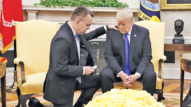 US President Donald Trump prays with American Pastor Andrew Brunson in the Oval Office of the White House on Saturday in Washington. Brunson returned to the U.S. after he was freed on Friday, having been detained for nearly two years in Turkey. - AFP