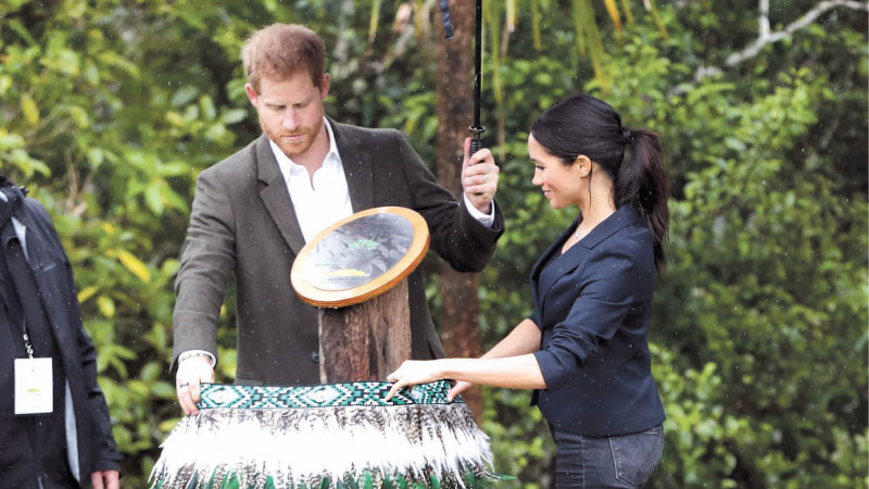 Prince Harry, Duke of Sussex and Meghan, Duchess of Sussex unveil a plaque at the Dedication to the Queens Commonwealth Canopy at the North Shore Riding Club in Auckland on Tuesday. - AFP