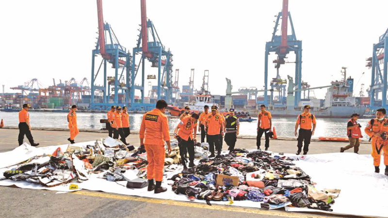 Indonesian search and resucue members place new evidence of personal items from the ill-fated Lion Air flight JT 610 at the Jakarta Port on October 30. - AFP