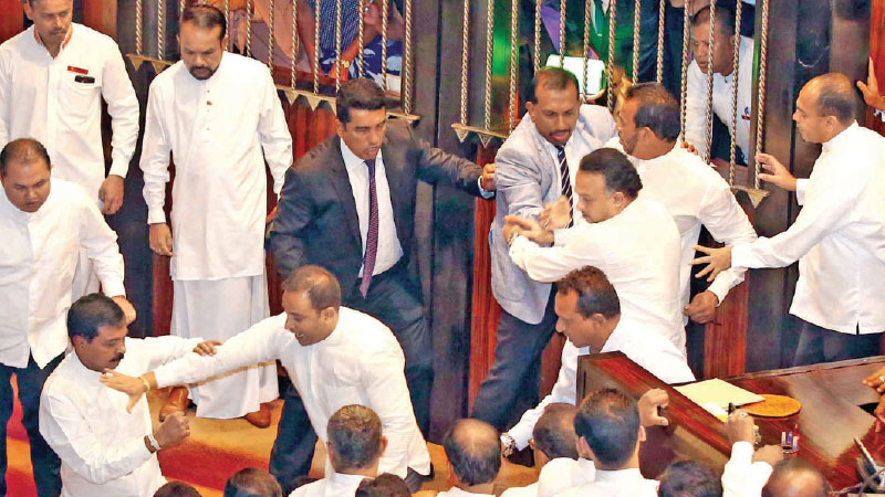 UNP MP Palitha Thevarapperuma who smuggled in a butter knife into the Chamber and behaved in a threatening manner being overpowered by fellow UNP MPs at yesterday's Parliamentary sitting. Pictures by Sajeewa Chinthaka.