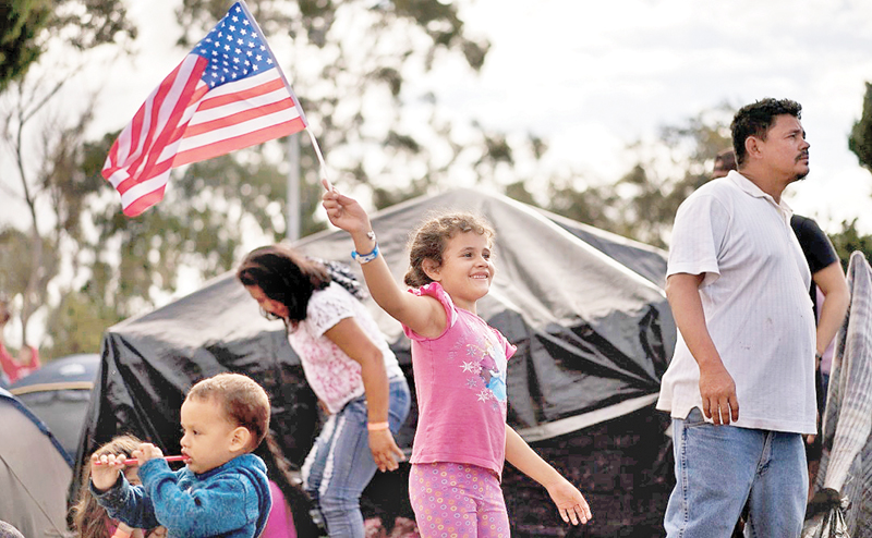 Seven-year-old Honduran migrant Genesis Belen Mejia Flores waves an American flag at a temporary shelter for Central  American migrants in Mexico.