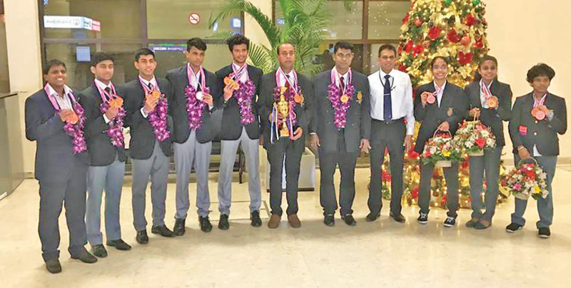 The Sri Lankan under 21 badminton team after their  arrival at the Katunayake Airport yesterday. Badminton president Nishantha Jayasinghe, coach Dhanushka Nilanga and manager K.G.I. Upendra are also present.