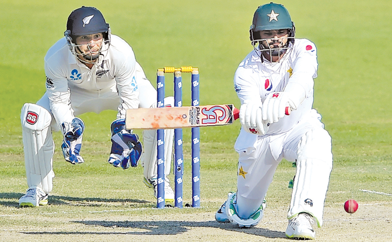 Pakistani batsman Azhar Ali (R) plays a shot as New Zealand wicketkeeper BJ Watling looks on during the third day of the third and final Test cricket match between Pakistan and New Zealand at the Sheikh Zayed International Cricket Stadium in Abu Dhabi on December 5. AFP