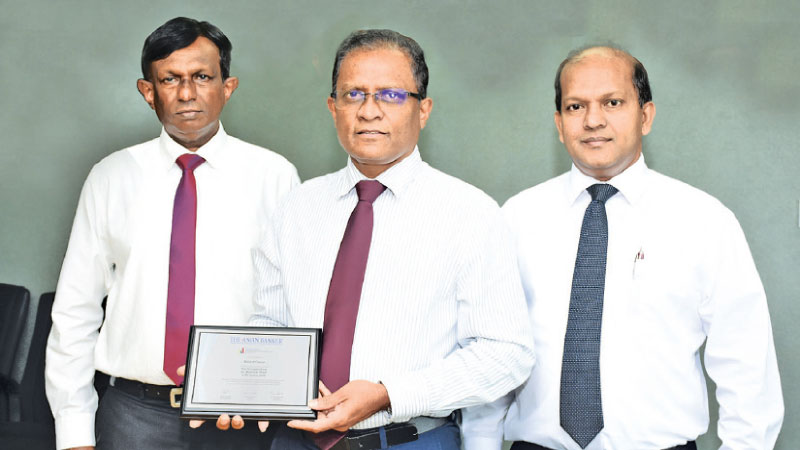 BOC, CEO and General Manager Senarath Bandara with the plaque flanked by BOC's CFO and Deputy General Manager Corporate and Offshore Russell Fonseka and Deputy General Manager Finance and Planning R.M.D.V. Jayabahu