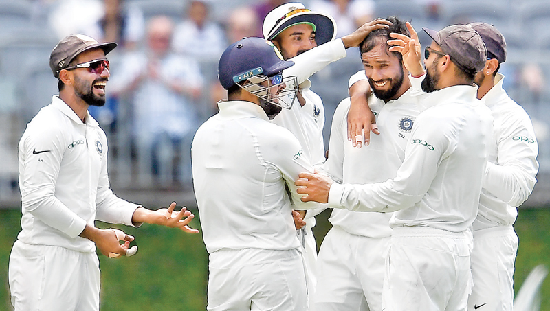 Hanuma Vihari (C) celebrating with teammates the dismissal of Australia's batsman Marcus Harris during day one of the second Test cricket match between Australia and India in Perth on Friday. AFP