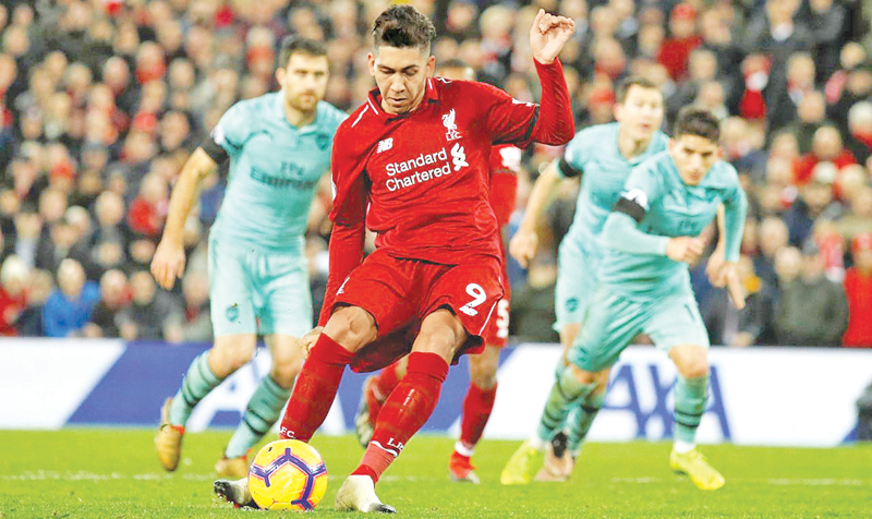 Liverpool's Roberto Firmino scores their fifth goal from the penalty spot to complete his hat-trick against Arsenal.
