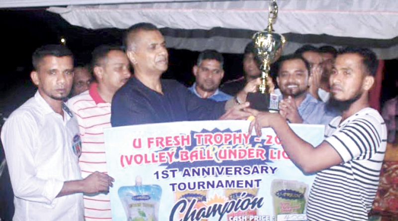 The skipper of Rangers Sports Club Volleyball Team, Akkaraipattu receiving the trophy from East West Beverage Managing Director Janaka Galappathi