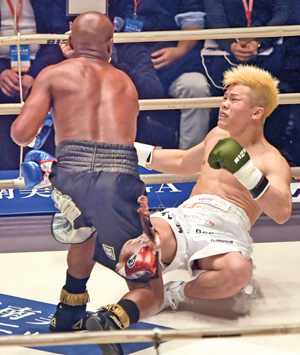 """US boxing legend Floyd Mayweather Jr (L) punches Japanese kickboxer Tenshin Nasukawa during an exhibition match at the Saitama Super Arena in Saitama on Monday. Mayweather won against Japanese kickboxing phenomenon Tenshin Nasukawa by a technical knock-out in the first round of a New Year's Eve """"exhibition"""" bout. - AFP"""