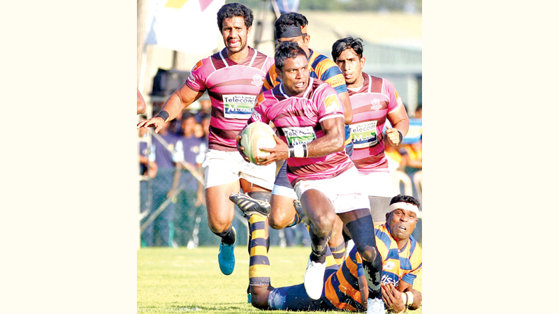 A Havelocks Sports Club player storms ahead after evading a tackle from a Army Sports Club player in their Dialog 'A' Division league Rugby match played at Air Force grounds, Ratmalana yesterday which Havelocks won 50-32. Picture by Samantha Weerasiri