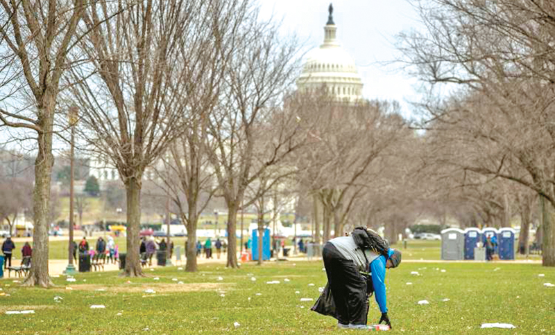 The Capitol building is visible as a man picks up garbage during a partial government shutdown on the National Mall in Washington on Sunday.