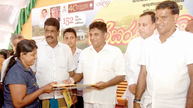 A recipient of a house receives the document for a house from the Minister.