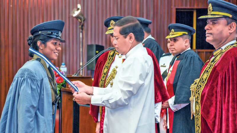 President Maithripala Sirisena  confers a diploma on a policewoman at the BMICH on Monday. Picture courtesy President's Media Division