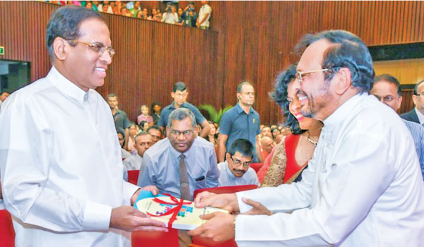 Dr. Mohan Lal Grero, MP presenting the first copy of  'Sri Lankan education system and the mismatch of  the job market' to President Maithripala Sirisena