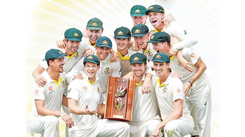 Australian players posing with the Warne-Muralitharan trophy after defeating Sri Lanka's in the second Test cricket match against Sri Lanka in Canberra on Monday. AFP