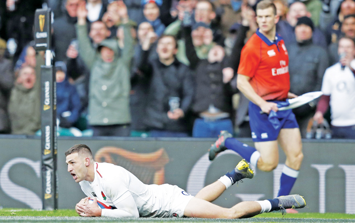 England's wing Jonny May dives over the line to score his third try during the Six Nations international rugby union match against France at Twickenham stadium on Sunday. - AFP