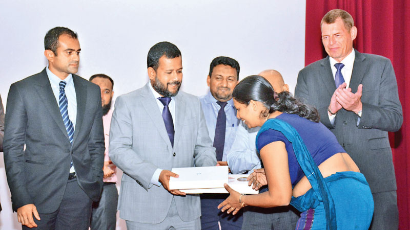 Minister Bathiudeen distributes Tablet PCs to NEDA field personnel at the event. Picture by Sarath Pieris