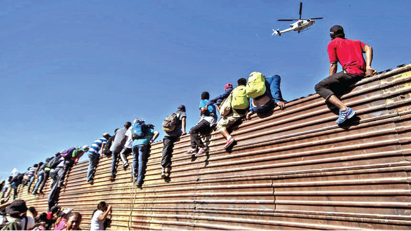 A US Police helicopter flies over migrants climbing the border wall on the US-Mexico border.