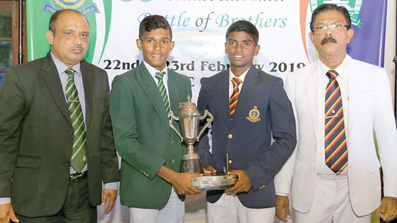 Isipathana skipper Madushika Samarawickrama and Thurstan captain Sandaru Dias (2nd and 3rd from left) pose with their school principals Premasiri Epa (Isipathana) and Lakshman Dias (Thurstan) and the Blackham Wijewardene Memorial Trophy that will be awarded to the winner of the match. (Picture by Rukmal Gamage)