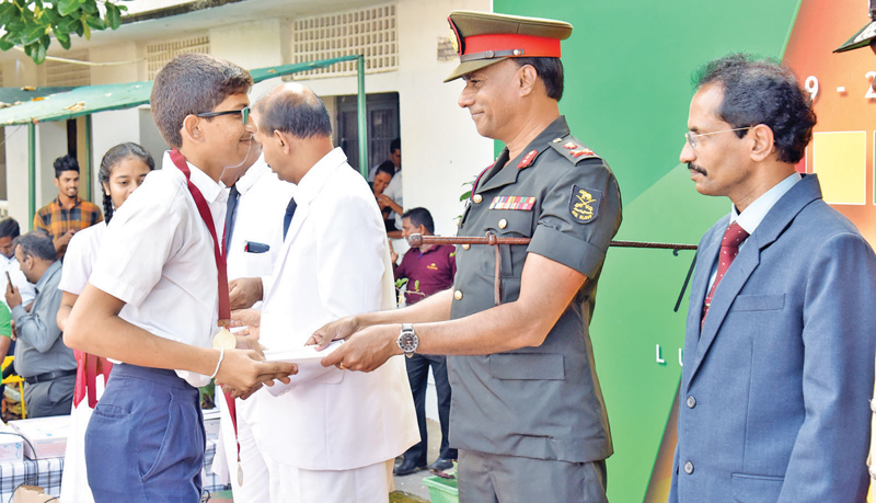 A student receiving a certificate from Major General L.F. Kasthuriarachchi