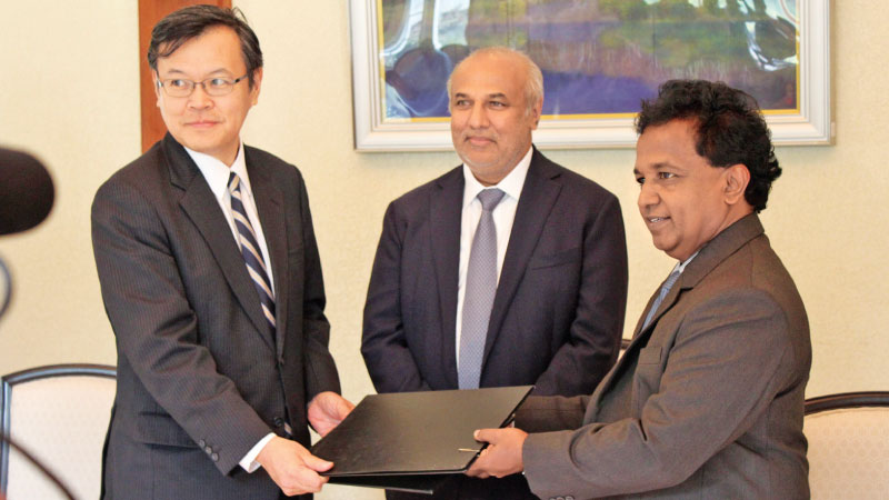 Ambassador of Japan in Sri Lanka Akira Sugiyama and Vice Chancellor of Rajarata University Dr. B.A. Karunaratne exchange the agreement. Town Planning, (Centre) Water Supply and Higher Education Minister Rauff Hakeem looks on. Picture by Sulochana Gamage