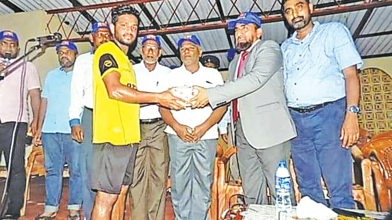 The skipper of the Udayasooriyan Sports Club, Thirukkovil receiving the champion trophy from High Court Judge N.M.Abdullah