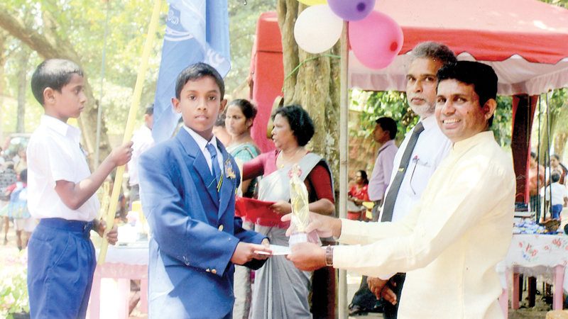 The best athlete (boys) Maharoo Pramuditha of Tissa House receives the championship cup from the WP Councillor Nandana Pathmakumara and the Principal Ranasinghe Indrasena. Picture by H.L. Sunil Shantha Kalutara Central Special Corr.