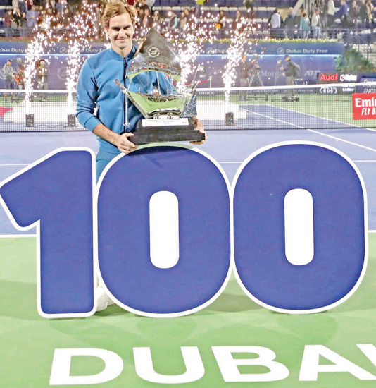 Switzerland's Roger Federer celebrates with the trophy after winning the final match at the ATP Dubai Tennis Championship in the Gulf emirate of Dubai on Saturday to record his 100th career title win when he defeated Greece's Stefanos Tsitsipas 6-4, 6-4 in the final of the Dubai Championships. - AFP