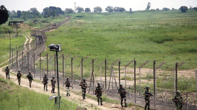 Border Security Force personnel patrol the fence at the international border in Jammu. - PTI
