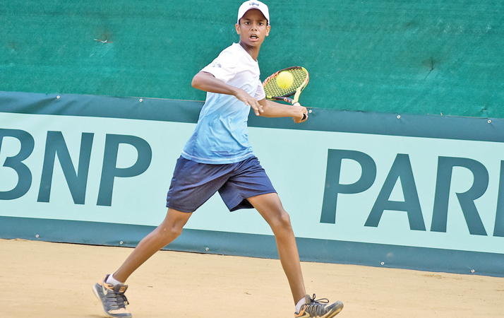 Thehan Wijemanne returns a forehand in the first singles match against Omanian's Muneer Tufail Al Rawahi
