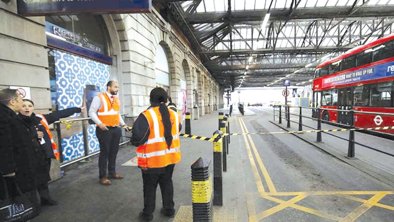 Security personel stand guard outside a police cordon at Waterloo Station, central London.