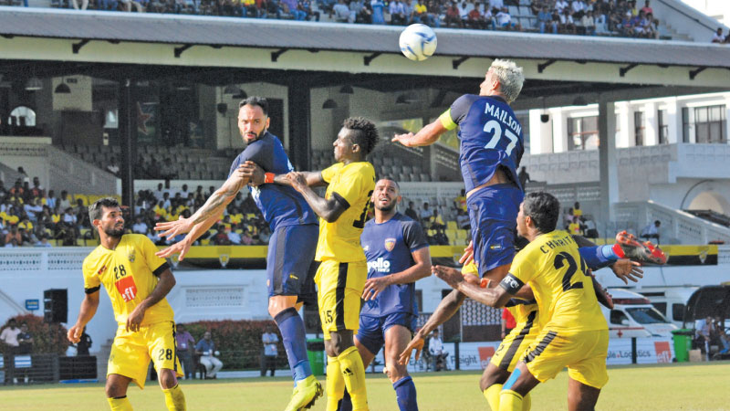 Chennaiyin's skipper and midfielder Mailson Veriato leaps high over Colombo FC players to get control of the ball.