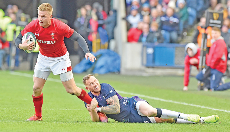 Wales' fly-half Gareth Anscombe (L) is tackled by Scotland's Byron McGuigan during the Six Nations international rugby union match at Murrayfield Stadium in Edinburgh on Saturday. – AFP