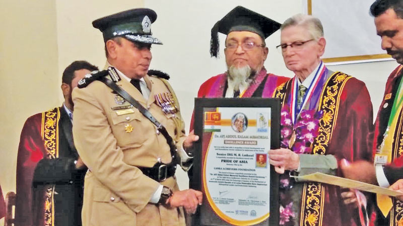 Prof. Vijay Shah of the Abdul Kalam Institute of Technological Sciences presents the honorary title of 'Pride of Asia' to Senior DIG M.R. Latiff, in Colombo recently.
