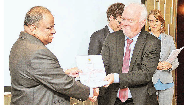 Ministry Secretary V. Sivagnanasothy presents a copy of the National Mine Action Strategy to Norwegian Ambassador Thorbjorn Gaustadsaether, yesterday. Picture by Hirantha Gunathilaka
