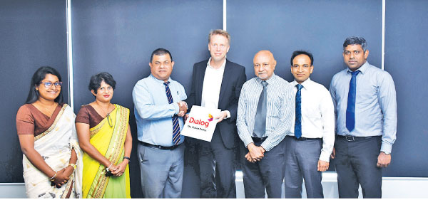 Dr. Rainer Deutschmann, Group Chief Operating Officer, Dialog  Axiata PLC (4R) handing over the agreement to Dr. D. M. A Kulasooriya,  Director General – NIBM (3L).