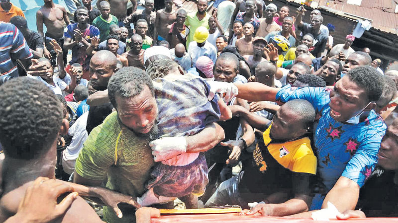 A child is rescued from the rubble of a collapsed building in Lagos, Nigeria on Wednesday.
