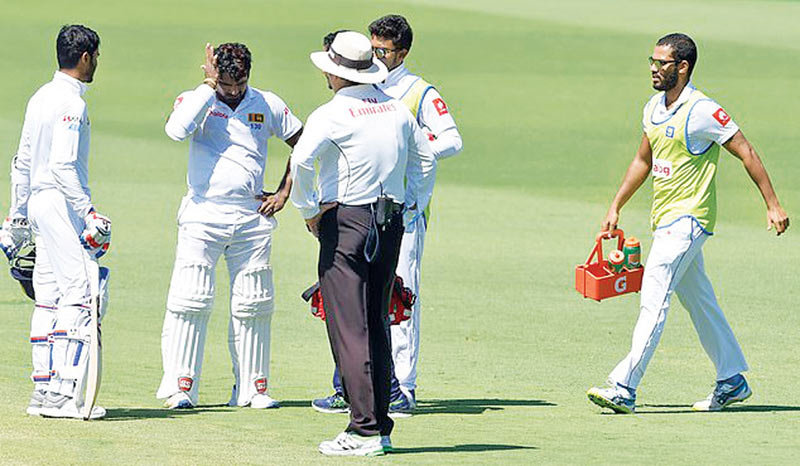 Batsman Perera rubs his head as a member of medical staff walks onto the pitch to treat him.