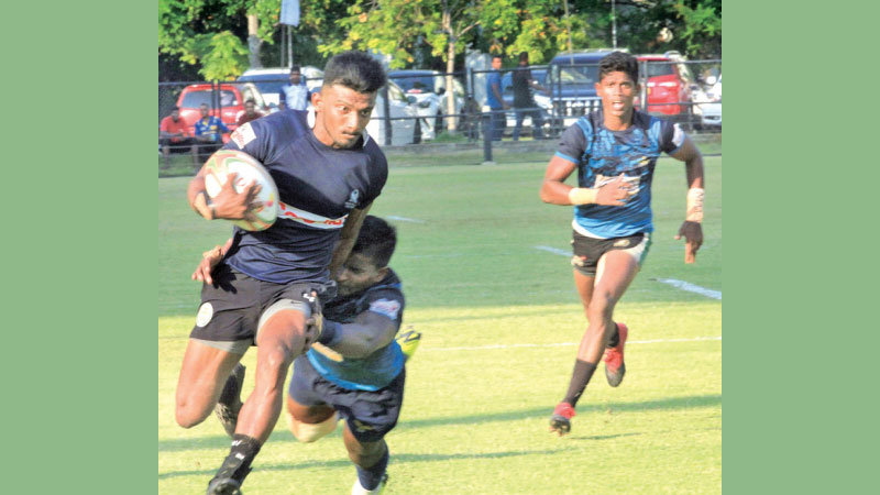 A Police player makes a break with an Air Force player making a desperate attempt to foil him in their Dialog Clifford Cup semi-final played at Race Course on Tuesday which  Air Force won 32-23 Picture by Sudham Gunasinghe