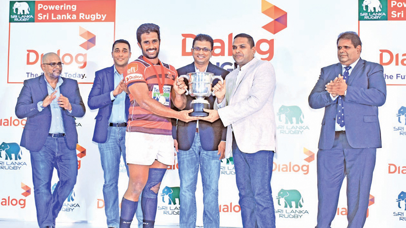 Havelock SC skipper, Niroshan Fernando receiving the coveted Clifford Cup from Minister of Telecommunication, Foreign Employment and Sports Harin Fernando. Supun Weerasinghe, Group Chief Executive, Dialog Axiata PLC, Thusitha Peiris, Secretary, Sri Lanka Rugby, Harsha Samaranayake, Senior General Manager – Brand and Media, Dialog Axiata PLC and Lasitha Gunaratne, President, Sri Lanka Rugby are also present.
