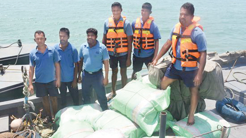 Navy personnel with some of the beedi leaves seized.