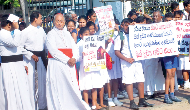 Archbishop of Colombo, Cardinal Malcolm Ranjith with schoolchildren at the protest against drugs, in Tudella, yesterday.