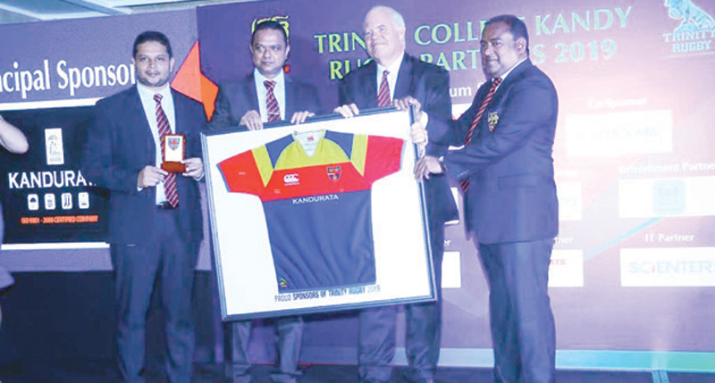 Awarding the sponsorship: Fron left: M.T. M. Naufal (Managing Director/Kandurata Umbrellas) and M.T.M. Nawushad (Chairman/Kandurata Umbrellas) handing over a new jersey with the sponsorship to Trinity Principal Andrew Fowler-Watt and chairman - scrummage of Trinity College - Siva Subramaniam