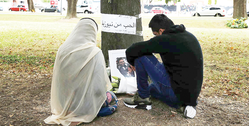 People visit at a memorial site for the dozens of people killed at the Al Noor mosque in Christchurch, New Zealand. The accused shooter will face 50 murder charges.