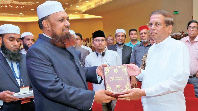 President Maithripala Sirisena is presented a copy of the simplified Sinhala language translation of the holy Quran, at the launch. Picture by Wasitha Patabendige