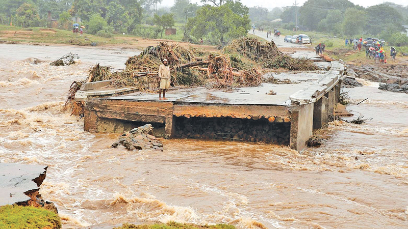 A man looks at a washed away bridge along Umvumvu river following Cyclone Idai in Chimanimani, Zimbabwe.