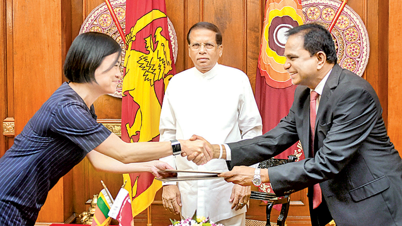 Power, Energy and Business Development Ministry Secretary Dr. Suren Batagoda and Canadian Commercial Corporation's Asian Region Director Yvonne Chin exchange the agreement in the presence of President Maithripala Sirisena at the Presidential Secretariat yesterday. Picture by President's Media Division.