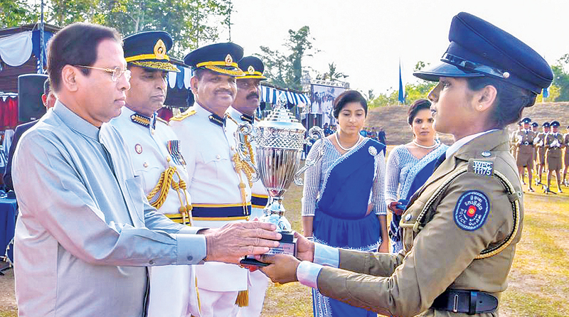 President Maithripala Sirisena presents a trophy to a woman constable, at the event. Picture courtesy President's Media Division