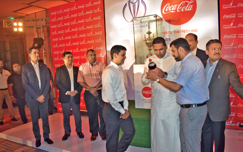 Sports Minister Harin Fernando wishing  the Sri Lankan cricket team for the ICC World Cup 2019 by pressing a button fix on a large Coca Cola bottle. Mayank Arora, Managing Director Coca Cola Beverages Ltd, Pankaj Sinha, Managing Director, Coca Cola Sri Lanka Ltd. Aravinda de Silva, former Brand Manager Coca Cola Cricket Pathway Program in Sri Lanka and vice captain of the 1996 Cricket World Cup winning team,  Crishantha Kapuwatte, Assistant Secretary Executive Committee Sri Lanka Cricket and Sundeep Bajoria